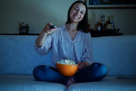 Young woman watching tv sitting on the sofa Фото со стока