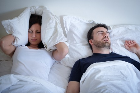 Tired and annoyed woman of her boyfriend snoring in the bed Standard-Bild