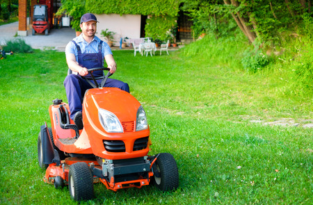 Gardener driving a riding lawn mower in a garden