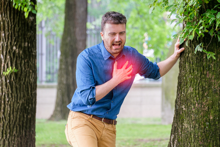 Severe heartache.Man pressing on chest with painful expression fist aid needed. Stock Photo