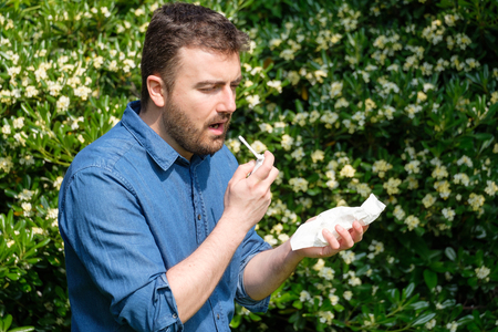 One man in blue shirt with allergy or cold, blowing his nose with tissue outside green trees background. Flu season, vaccination. Stock Photo