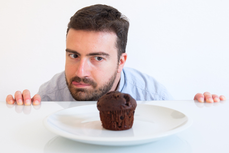 Sweet tooth man on diet tempted by chocolate muffin