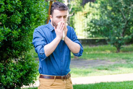 Man in public park blowing his nose and suffering from pollen allergy.