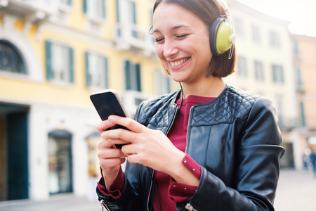 Happy student listening mp3 music outdoor and typing message in the city street