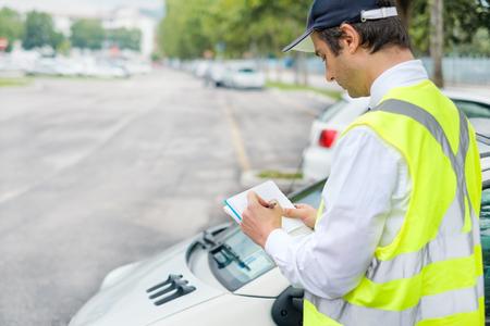 Addetto al parcheggio che scrive un biglietto per una violazione del parcheggio