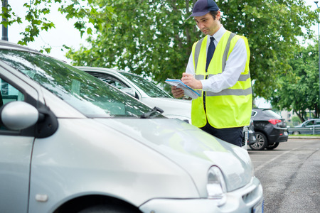 Parking officer writing a ticket for a parking violation