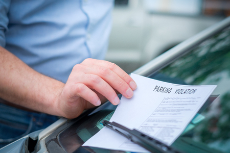 Man finding a ticket fine under the car windscreen because of parking violation Foto de archivo