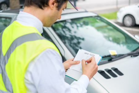 One parking warden writing a ticket for a parking violation