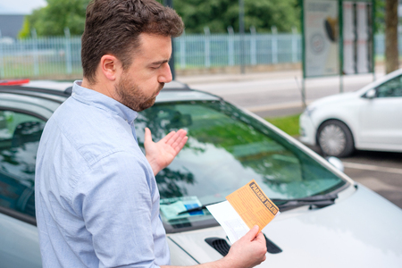 Angry man looking on parking ticket placed under windshield wiper Stockfoto