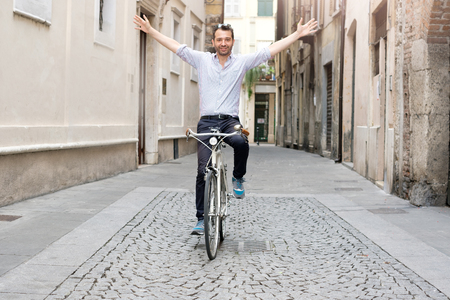 Handsome successful man on his bike in the city riding without hands