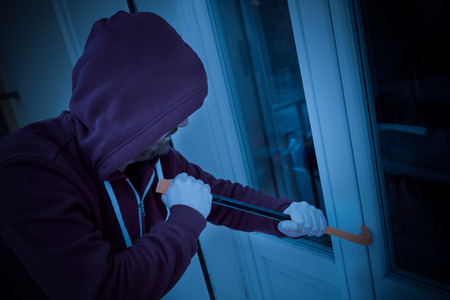Hooded housebreaker forcing window lock to make a theft in a house at night Stock fotó