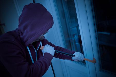 Rompedor encapuchado forzando la cerradura de la ventana para hacer un robo en una casa por la noche Foto de archivo