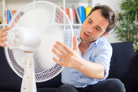 Man sweating and trying to refresh in summer haze Stock Photo