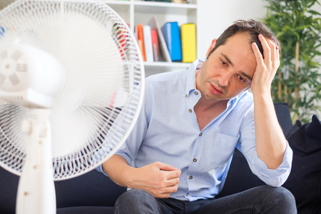 Man refreshing with electric fan against summer heat wave Stock Photo