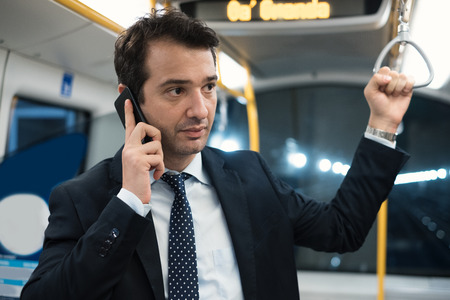 Portrait of businessman talking on his mobile phone while is going to work