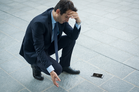 Sad businessman after his phone is fallen and crashed on the ground
