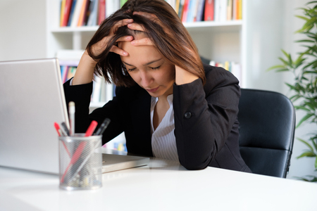 Overworked woman feeling exhausted because of too many job hours