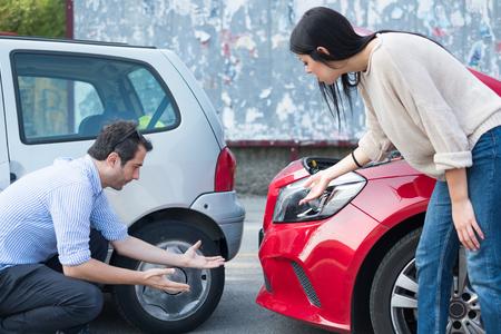 Man and woman arguing and examining cars after crash