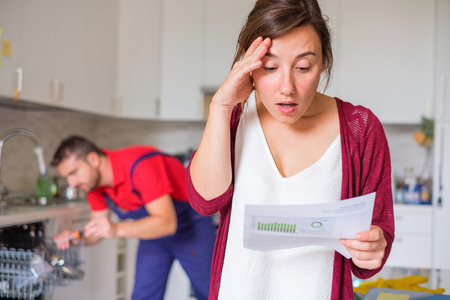 Housewife shocked after reading repair cost estimate of domestic appliance Stock Photo