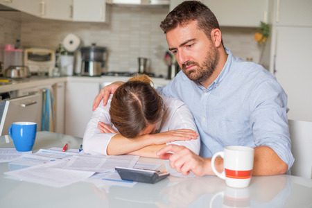 Husband consoling his wife about family financial trouble
