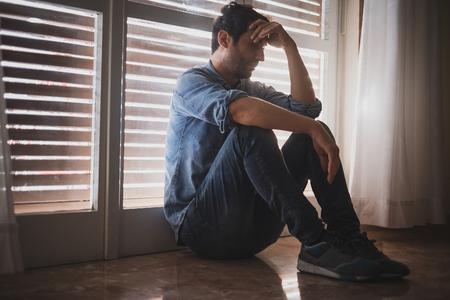 Uomo depresso seduto vicino alla finestra
