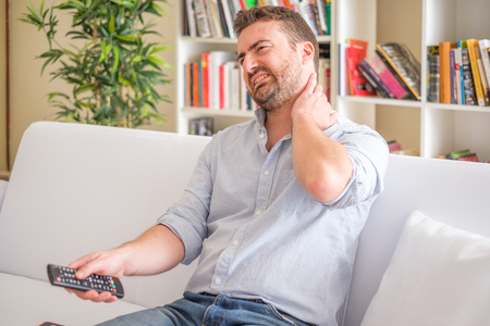 Man suffering neck ache seated on the sofa watching television with bad posture