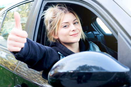 Cheerful girl driving her new car ready to go Standard-Bild