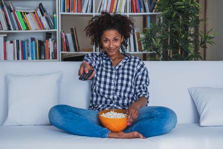 Glückliche Frau, die zu Hause mit Fernbedienung sitzt und fernsieht Standard-Bild