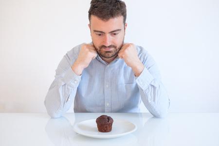 Hombre con golosos tratando de resistir al pastel de muffins de chocolate dulce