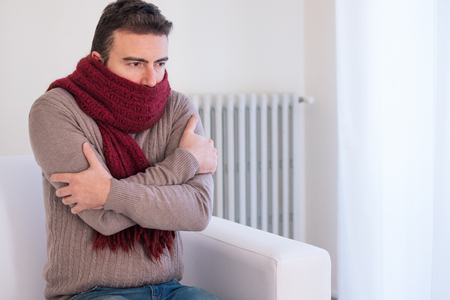 Man freezing and shivering at home because of winter cold