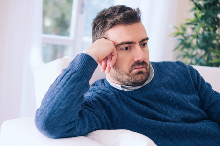 Upset man feeling negative emotions at home