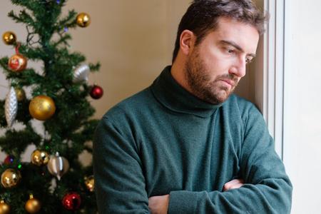 Hombre en soledad sintiéndose mal durante el día de Navidad