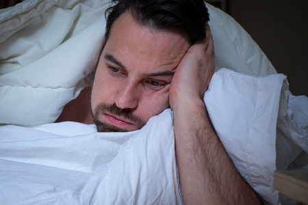 Stressed sleepless man expression lying in the bed