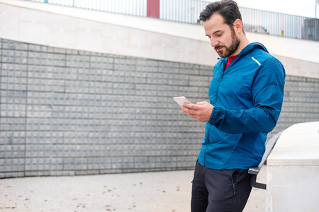 Athletic guy doing training session with smartphone