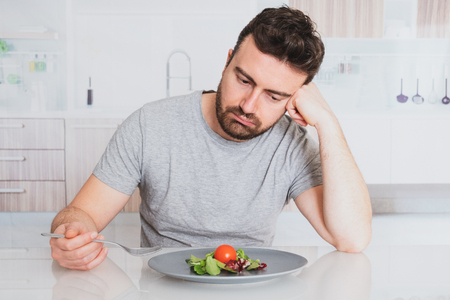 Worried man hungry and starved with salad Stock Photo