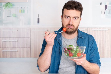 Sad man forced to eat salad for weight loss Archivio Fotografico