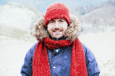Portrait of young man under snow flakes in cold weather Stock Photo