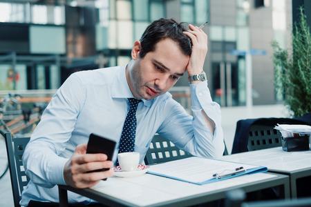 El empresario enojado y estresado no puede relajarse debido a demasiado trabajo. Foto de archivo