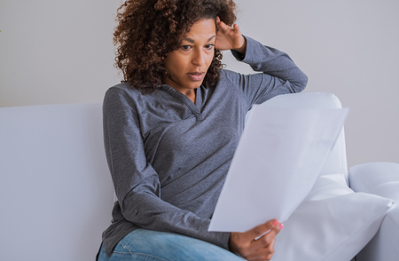 Worried black young woman reading bad news at home
