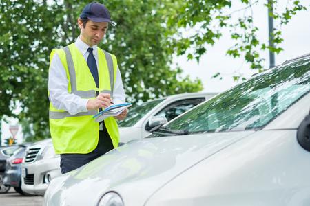 Mitarbeiter des Parkpolizisten bestrafen falsch geparktes Auto Standard-Bild