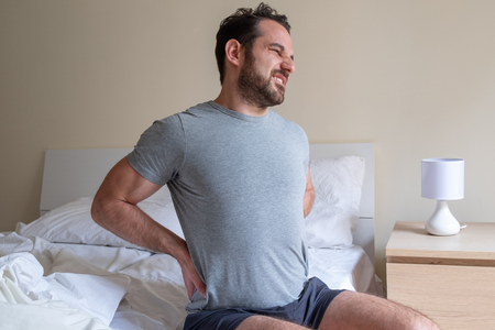 Man feeling backache after sleeping in bed