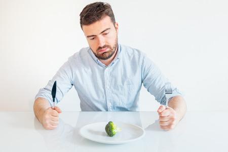 Hombre triste y hambriento viendo comida de mala dieta Foto de archivo