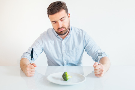 Sad and hungry man watching poor diet meal Banque d'images