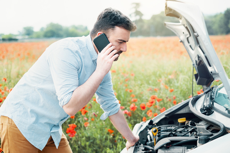 Stressed driver after car breakdown calling roadside service Stock Photo