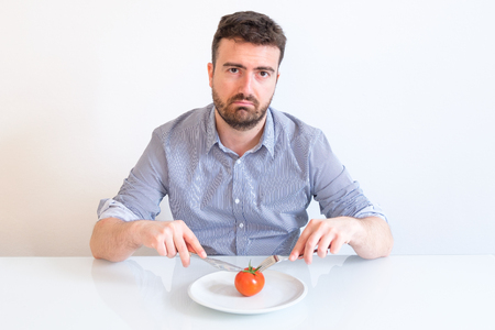 Sad and hungry man watching poor diet meal Imagens
