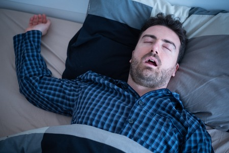 Male suffering sleep apnea lying in the bed