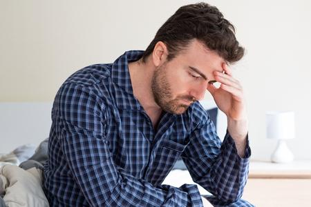 Homme se sentant mal et assis sur le lit