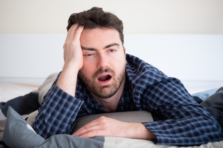 Man with sleep problem in his bed at home Stock Photo