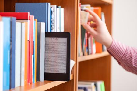 Mano de estudiante manteniendo tableta digital en estantería en la biblioteca de la escuela Foto de archivo