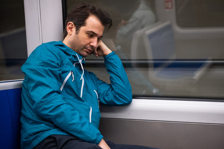 Sleepy young man feeling sad in the train in the morning Imagens